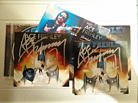 Indoor photo of autographed Ace Frehley album covers.